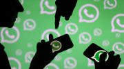 FILE PHOTO  Men pose with smartphones in front of displayed Whatsapp logo